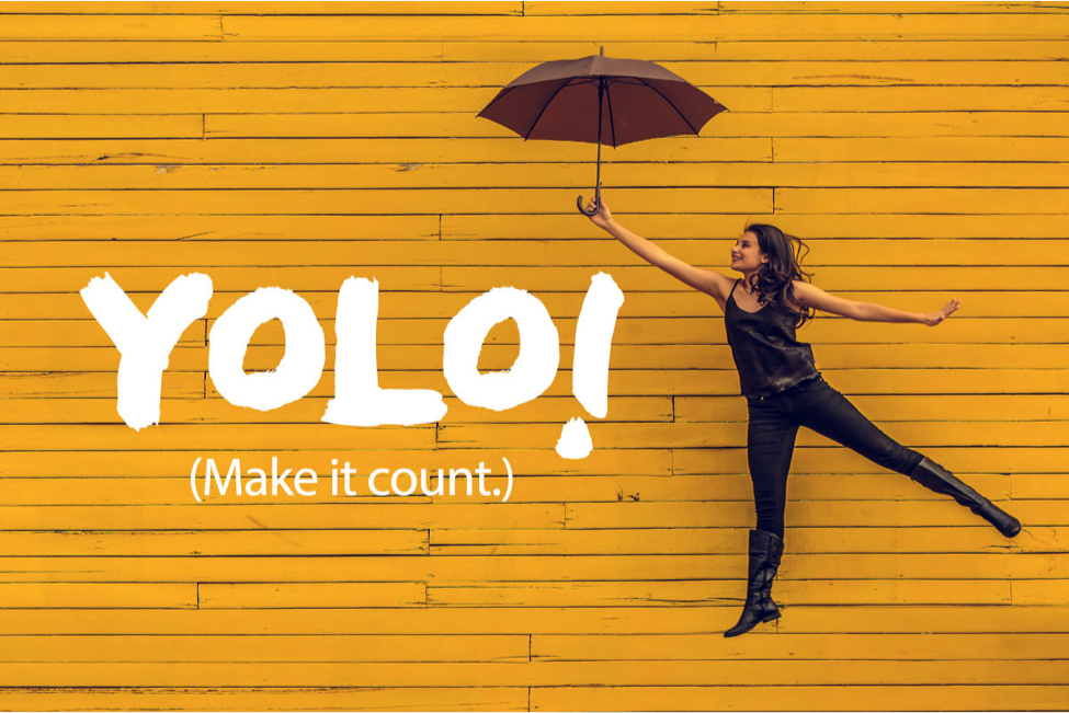 YOLO make it count woman jumping in front of yellow background with umbrella