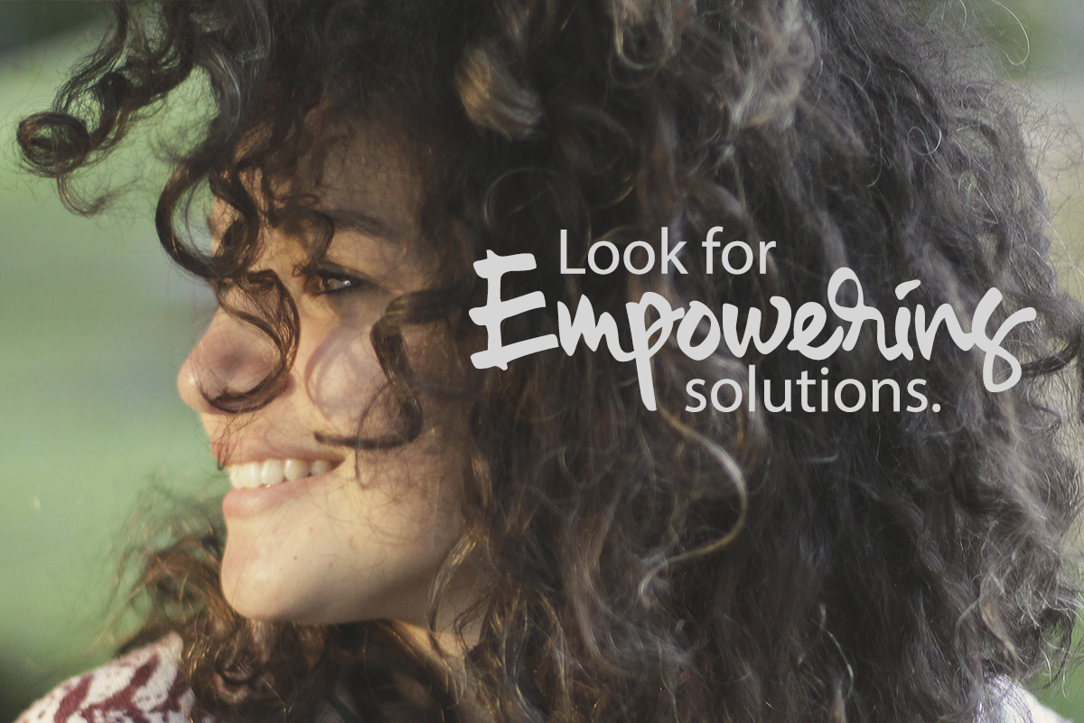 Look for empowering solutions. Woman with curly hair looking to the side.