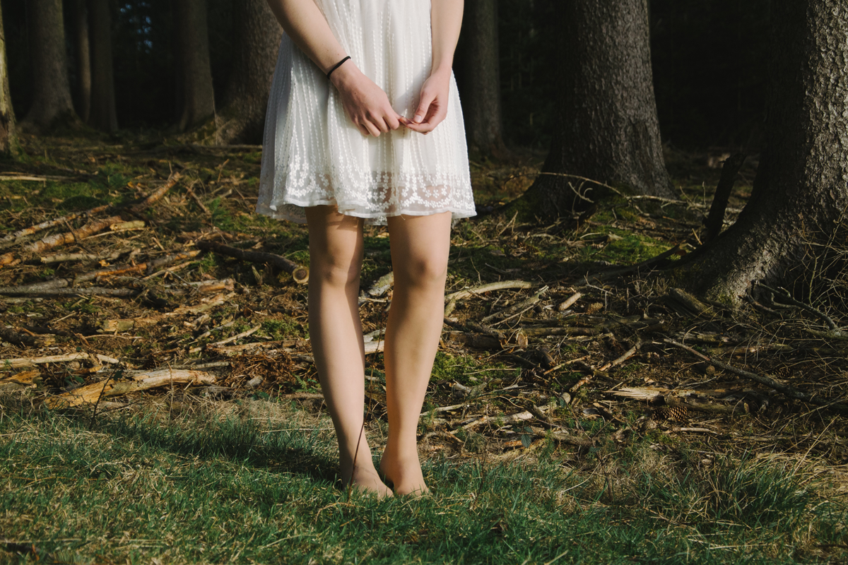 Young woman in a white dress standing on grass with woods in the background