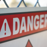 "warning sign that says ""danger"" on a chain-link fence"
