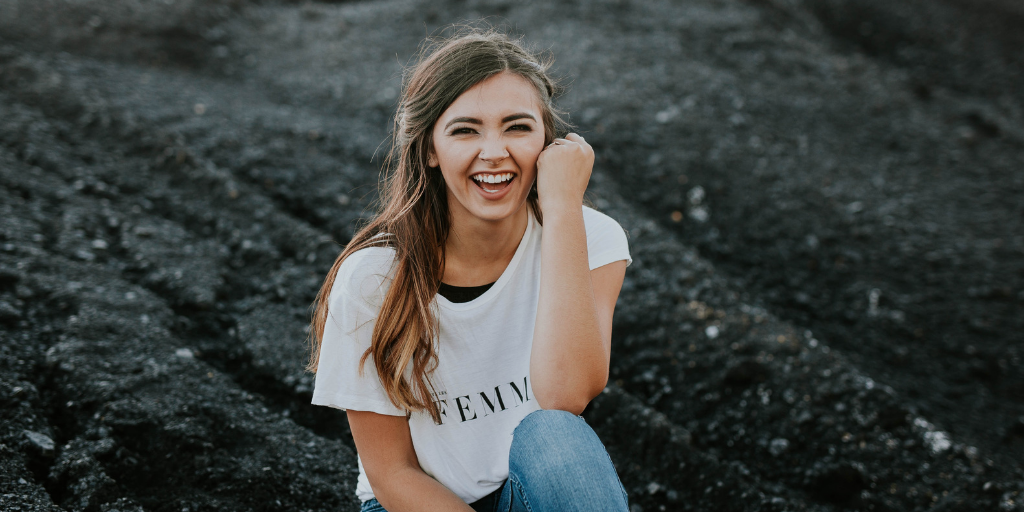 "Woman wearing shirt reading ""Femme"" sits on hill, smiling."