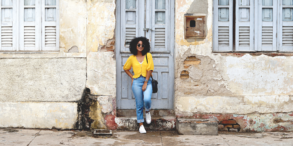 Woman leans against rustic wall with relaxed stance